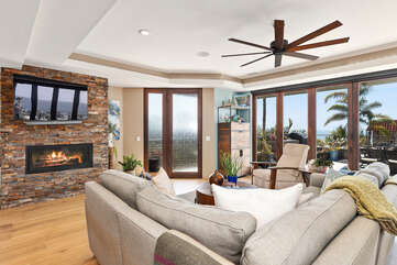 A large TV and fireplace will welcome you in this large living room and amaze you with panoramic views of the ocean.