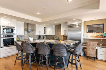 The kitchen has a bar with seating for up to 5 people.