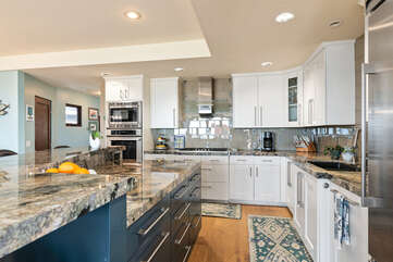The kitchen features a beautiful granite countertop and white cabinets.