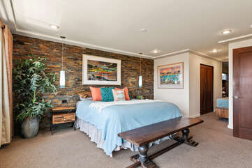 Master bedroom has a beautiful stone feature wall.