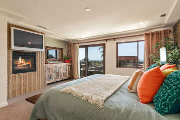 The master bedroom features ocean views, TV, and fireplace.