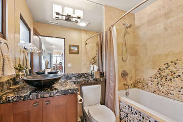 This shared bathroom has a shower/tub combo and features a beautiful rock mosaic with granite countertops.