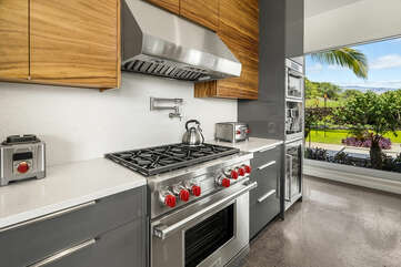 Oven range with red knobs, alongside other stainless steel appliances.