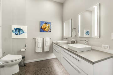 His and her vanity sinks in front of a walk-in shower and the toilet.