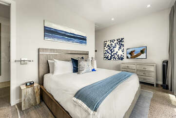 Mer Suite with large bed, dresser, and standing fan.
