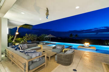 Cushioned couch and armchairs on the back lanai by the pool.