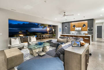The spacious living area of this Mauna Kea house rental with couches, armchairs, and unique glass-topped table.