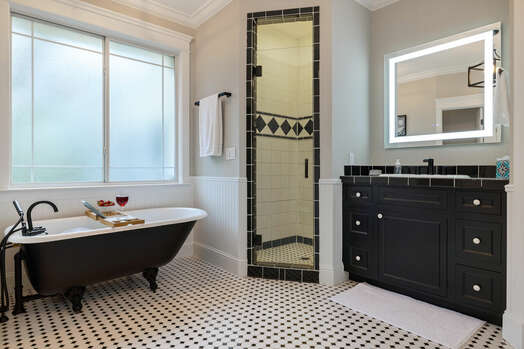 En suite with a shower, soaking tub, and two separate vanities with lighted mirrors