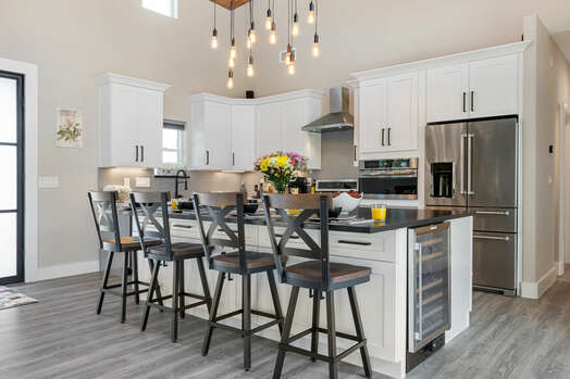 Gourmet display kitchen with 5-seat center island and stocked to the hilt for any chef