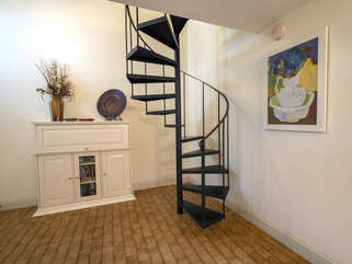 Enter this bright villa with spiral staircase, beautiful art, and welcoming decor.