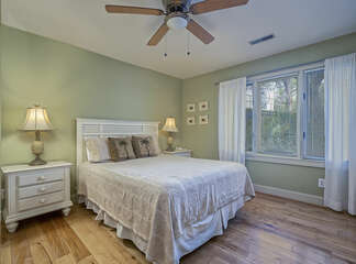 A comfortable queen bed, ceiling fan and large windows.