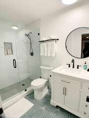 The shared bathroom down the hall features modern finishes and a large shower with two shower heads.