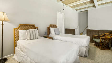 Loft bedroom with two beds and seating area