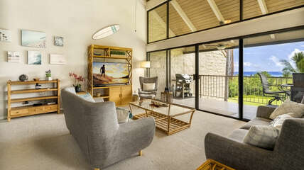 Spacious living room with comfortable chairs overlooking large lanai