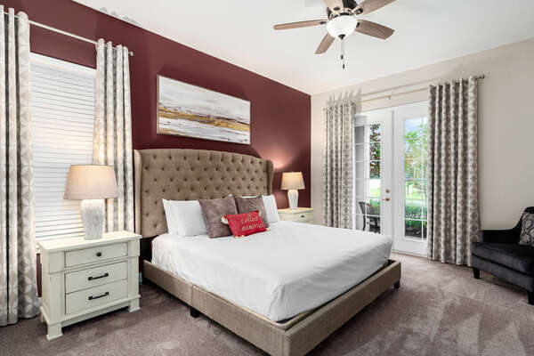 Master suite with a king-size bed and patio access