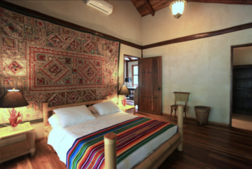 Master bedroom 2, with a king-size bed, en-suite bathroom, and access to the balcony