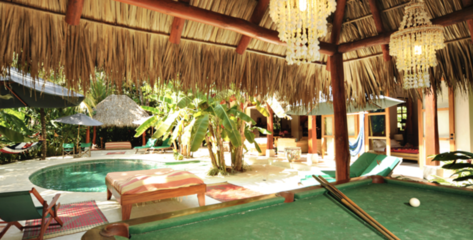 A pool table under the ranchito and next to the pool
