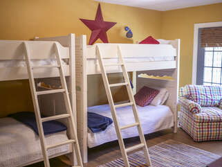 A large bunk room with four twin beds Access to the back porch and steps leading down to the ping pong table