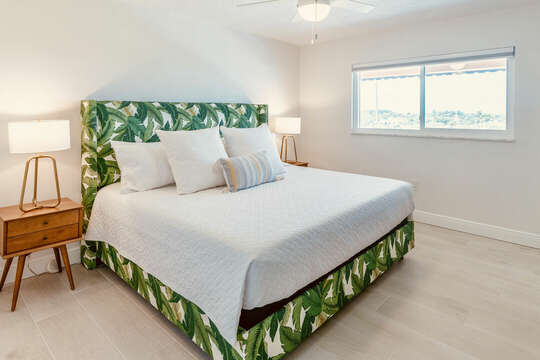 First guest bedroom with a king bed and a big screen TV.