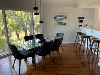 Glass top dining table comfortably seats 6 and is open to the breakfast bar
