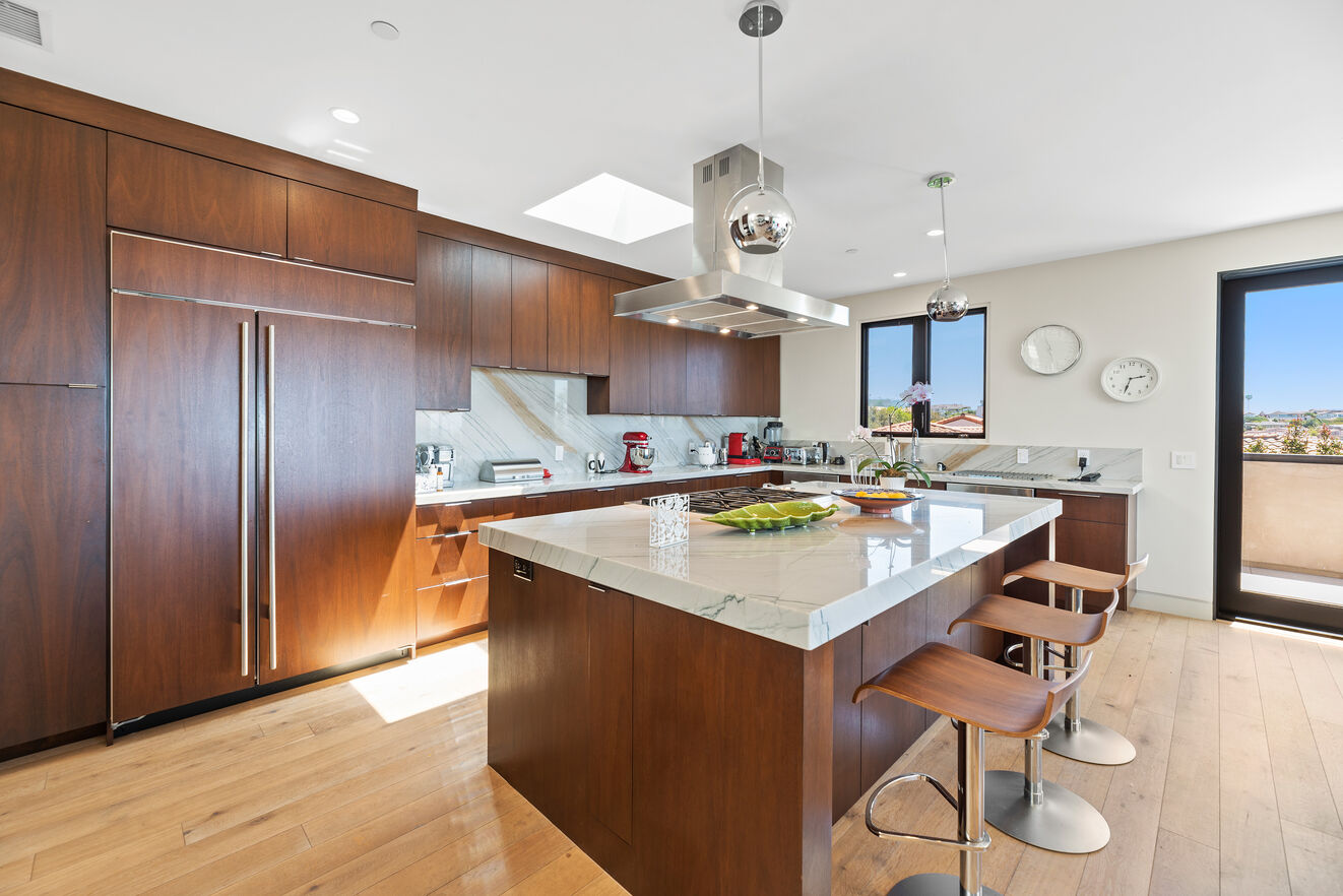Large open kitchen with three bar stools at the island