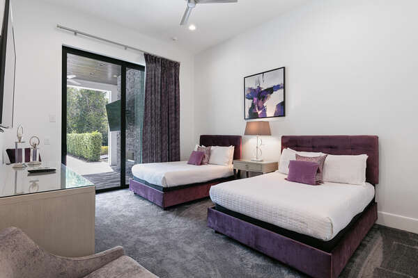 First-floor bedroom furnished with two full-size beds with access to the covered patio