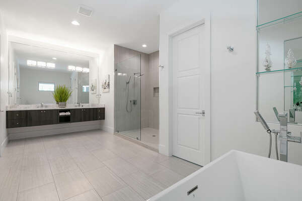 The ensuite bathroom has dual vanities, a walk-in shower, and a garden tub