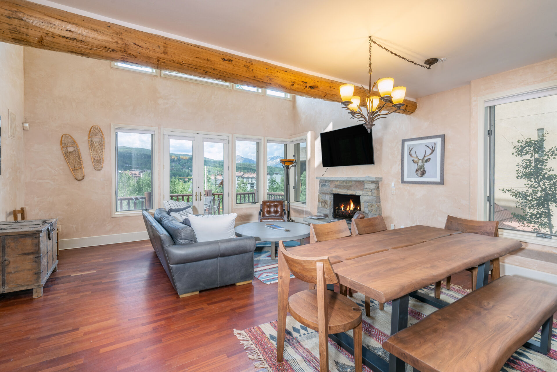 Spacious living and dining room with wood floor and wood beam