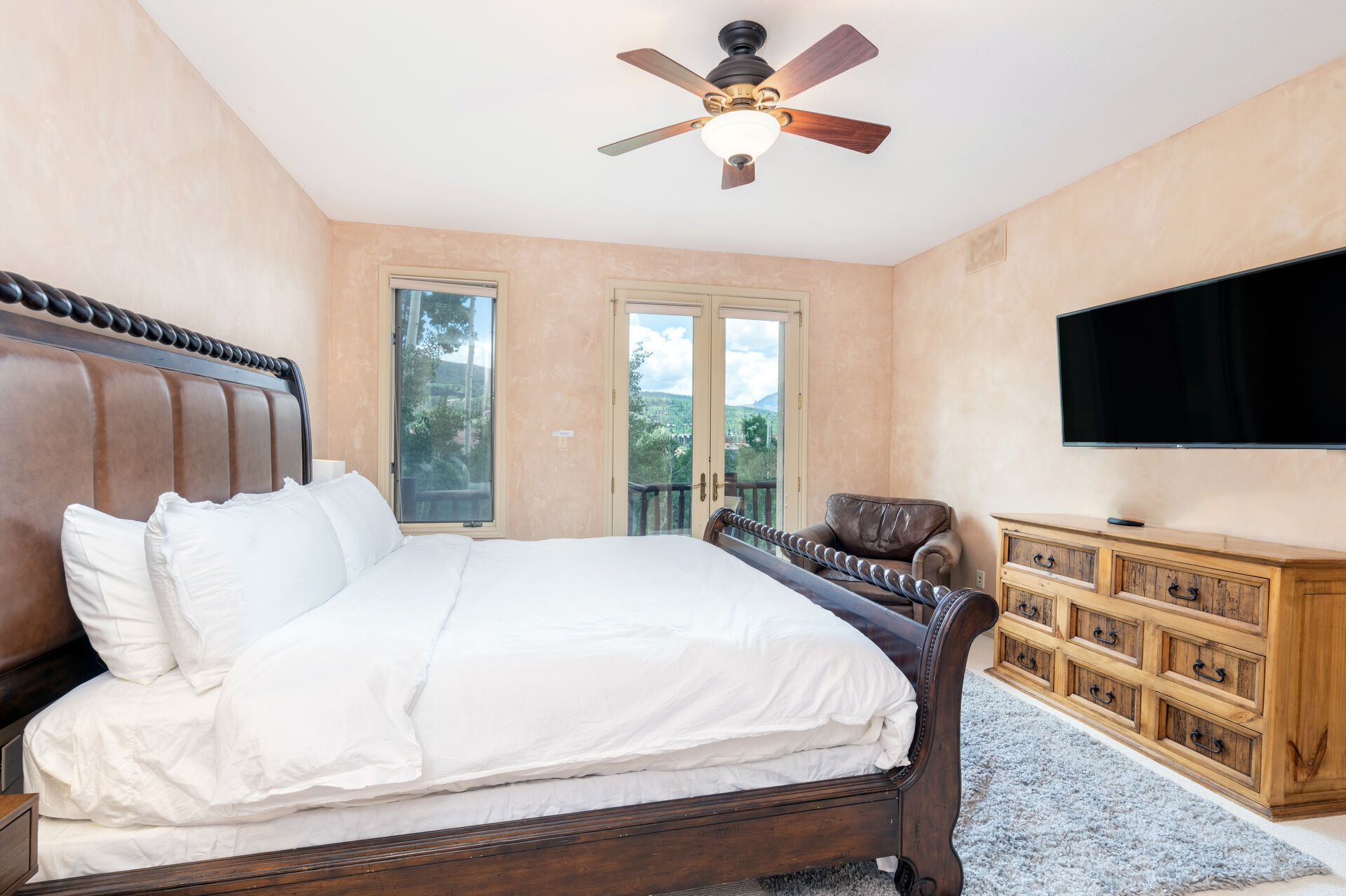 Bedroom with large bed and wood sleigh frame and wood chest of drawers