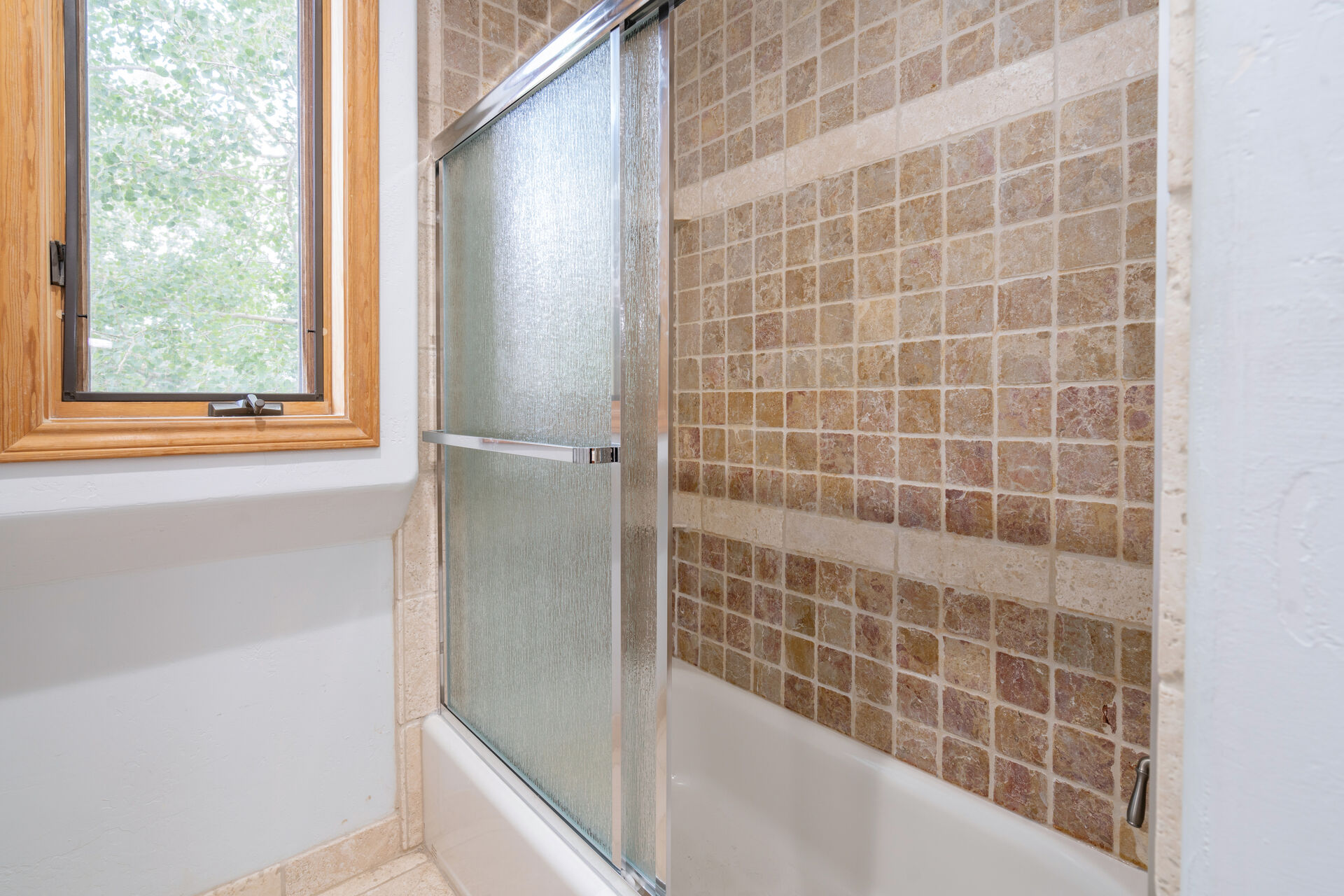 Brown tile tub and shower in bathroom