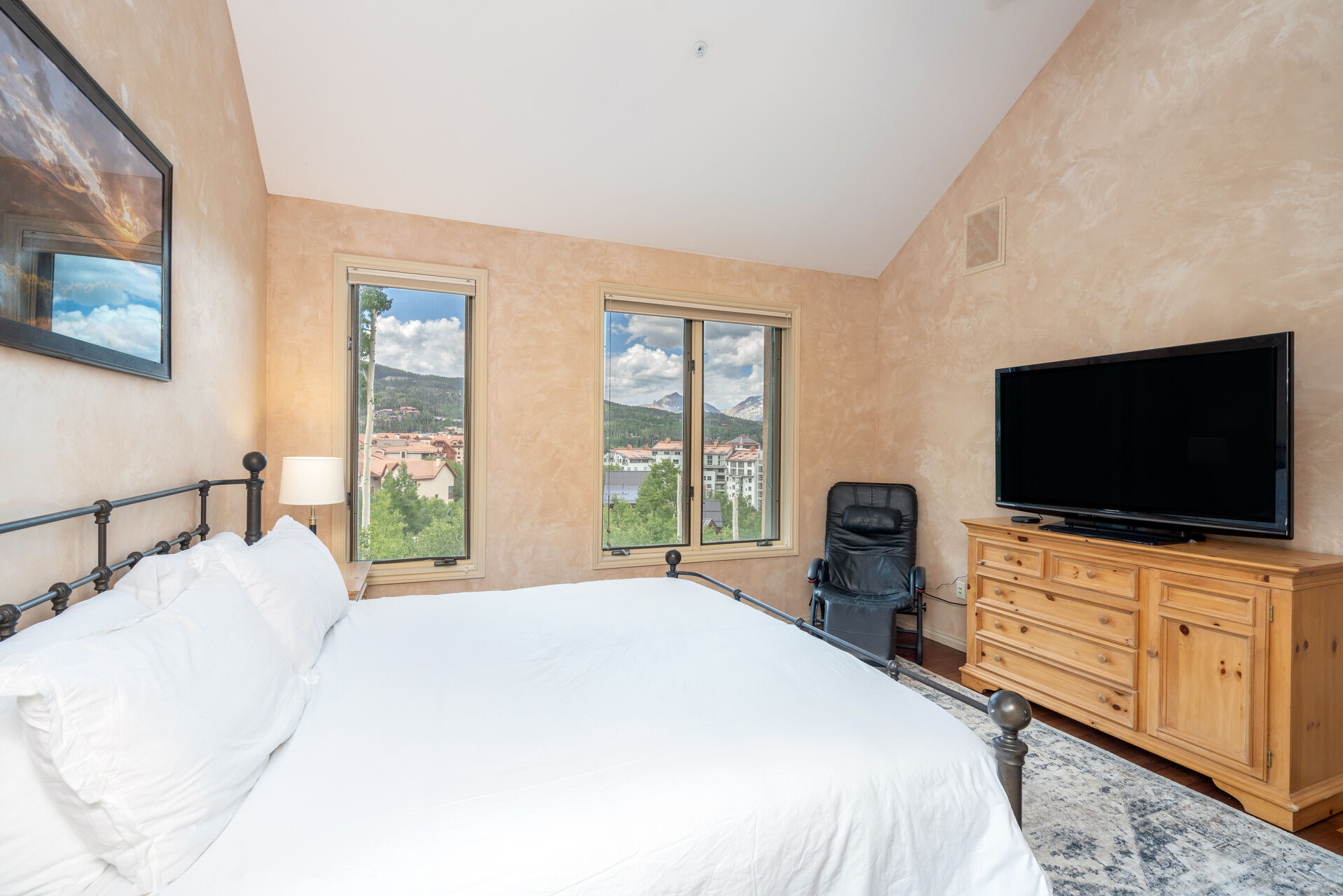 Bedroom with white bed and wood chest of drawers