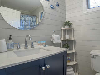 The renovated guest bath has ship lap walls and a tub/shower combo