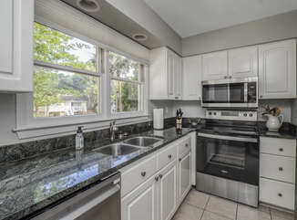 The kitchen is to your left and has updated with new granite counters, back splash, and stainless steel appliances.