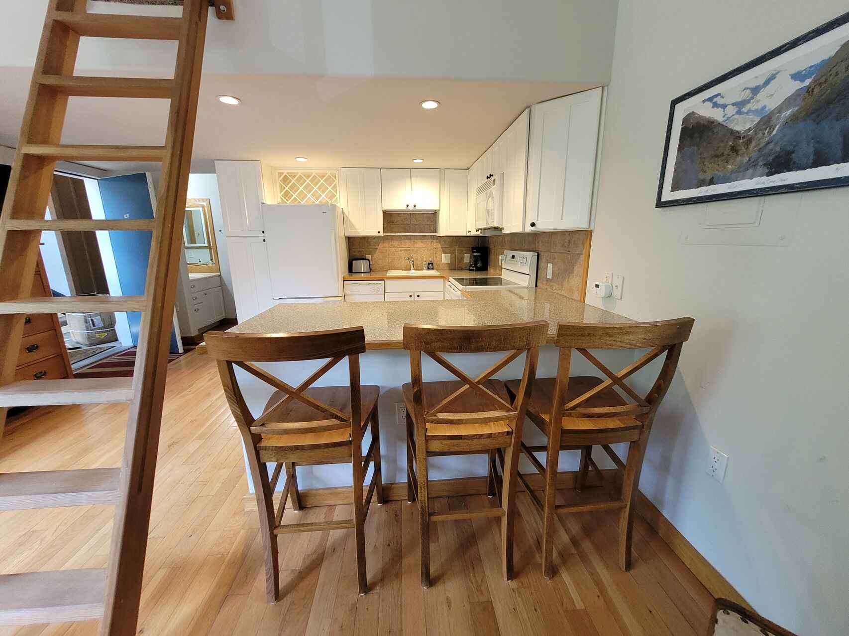 Kitchen with three wood seats and white cabinets
