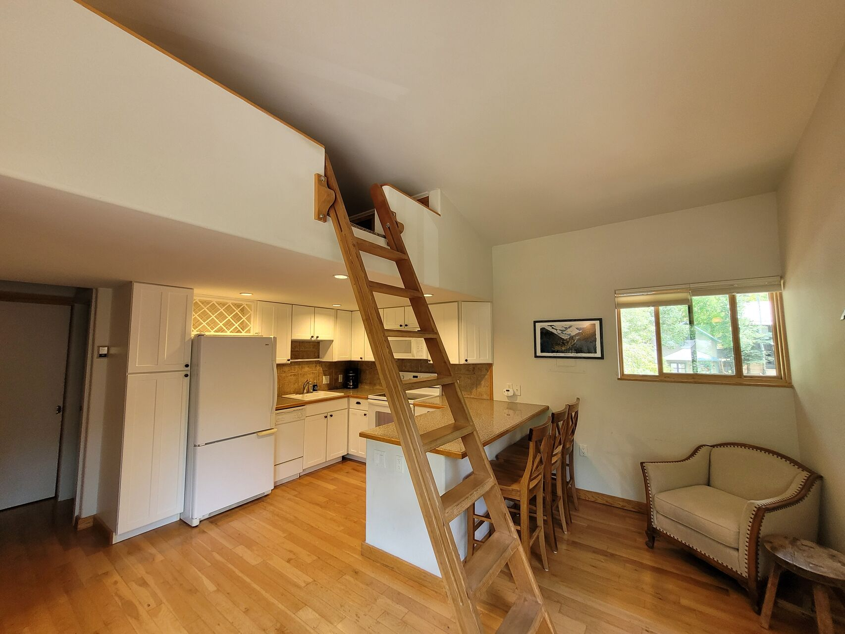 Living area with wood ladder and white cabinets