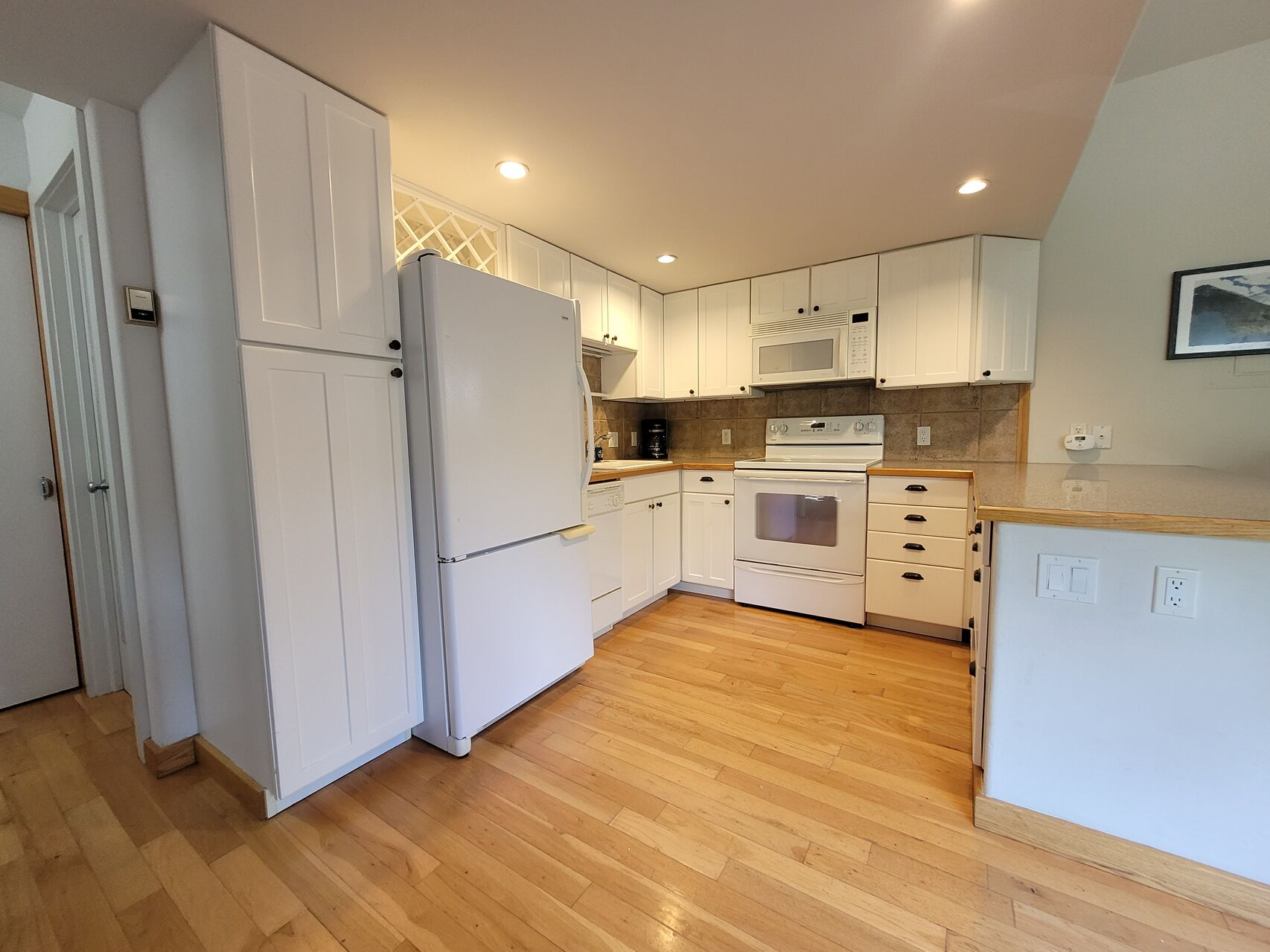 Kitchen with white appliances and wood floors