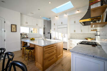 Simplistic white full kitchen including an island and large range.
