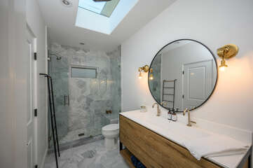 Full bathroom with a walk in shower & his and hers sinks connects to the second bedroom.