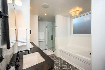 Large bathroom features a walk in shower and separate soaking tub