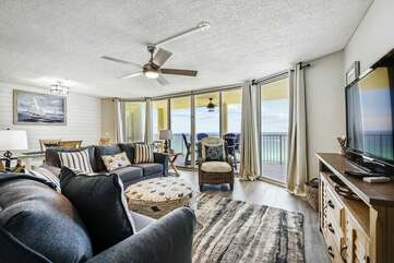 Spacious living room with plenty of seating and large flat screen TV, beautiful view of the Gulf with balcony access
