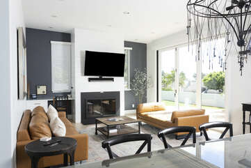 Living room with smart TV and open windows for ocean/ sunset views
