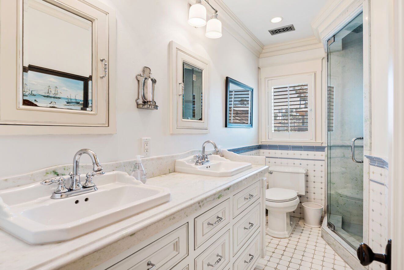 Shared upstairs bath with double vanities and shower