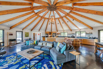 Massive great room with open floor plan, floor-to-ceiling windows, and one-of-a-kind wooden ceiling beams