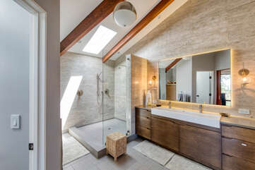Spacious master with LED-lit mirror, beautiful double sink vanity, and shower