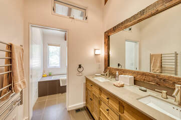 Shared guest bathroom with long mirror and double sink vanity