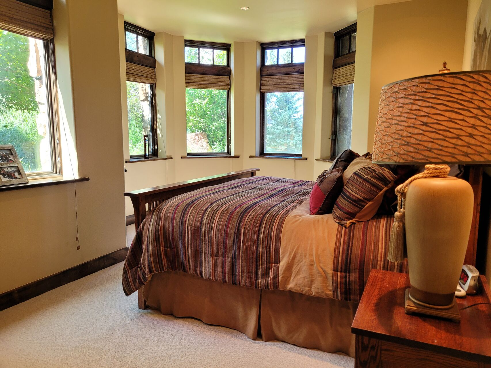 Bedroom with large bed with striped cover