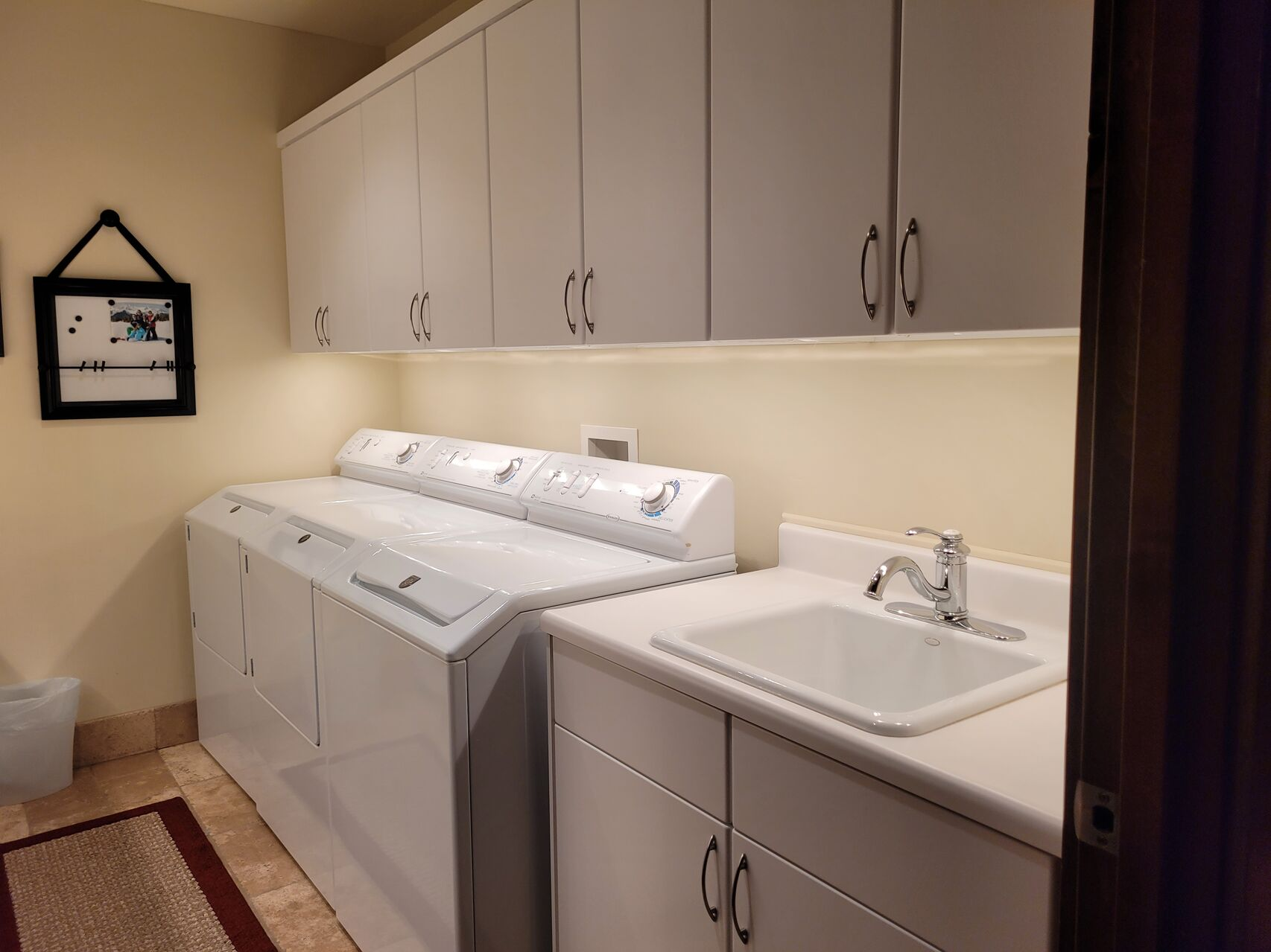 Laundry room with large washer and dryer and utility sink
