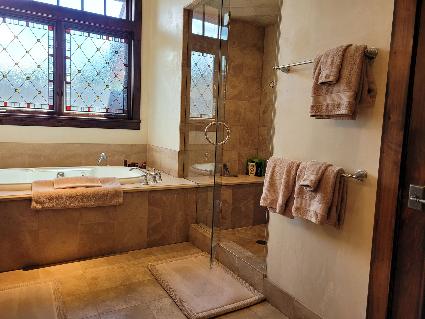 Luxury bathroom with brown tile and walk-in shower