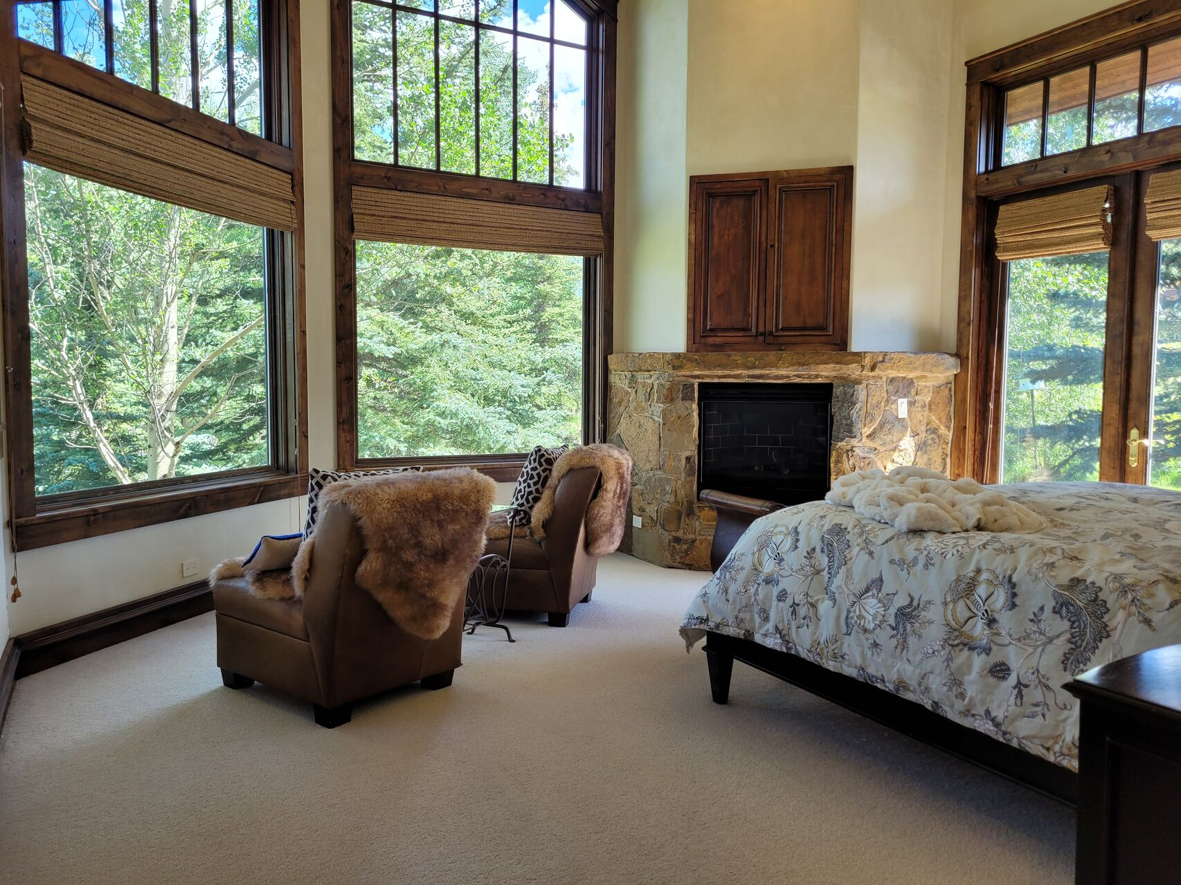 Large bedroom with seating area overlooking tree view