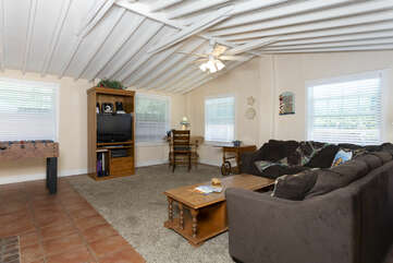 This cozy living room has vaulted ceiling with a TV and foosball table.